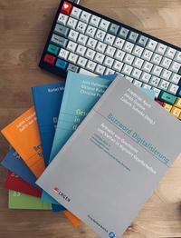 Die Bücher der Reihe liegen gestapelt neben einer Tastatur auf einem Schreibtisch.