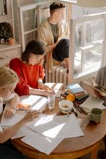 Drei Personen schreibend an einem Tisch