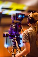 Blonde Frau hinter einer Videokamera.