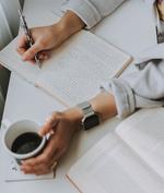 Hände, die in ein Notizbuch schreiben